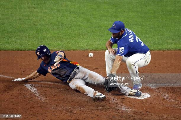 Myles Straw of the Houston Astros slides into home plate to score on a wild pitch as pitcher Greg Holland of the Kansas City Royals covers during the...