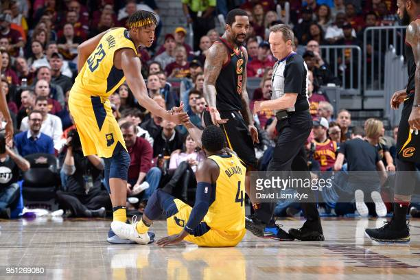 Myles Turner of the Indiana Pacers helps Victor Oladipo of the Indiana Pacers off of the flor during the game against the Cleveland Cavaliers in Game...
