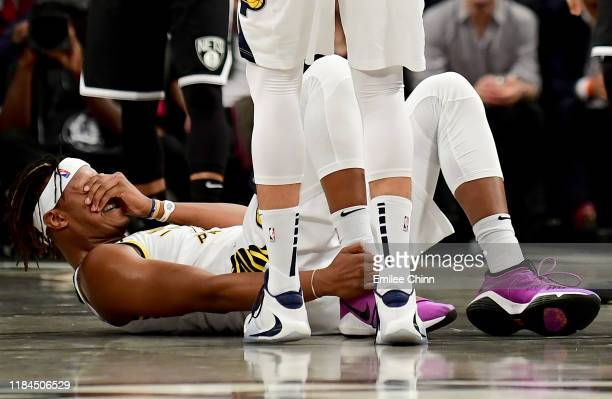 Myles Turner of the Indiana Pacers holds his ankle after getting hurt in the first half of their game against the Brooklyn Nets at Barclays Center on...