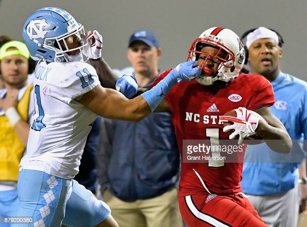 Myles Wolfolk of the North Carolina Tar Heels is called for a facemask penalty against Jaylen Samuels of the North Carolina State Wolfpack during...