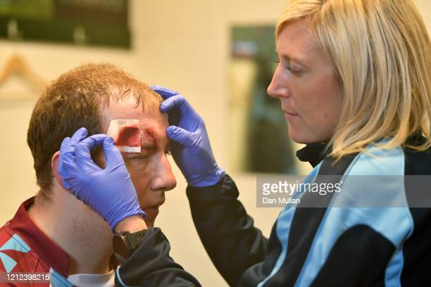 Mylo Connell of OPMs receives treatment to a head injury following the Lockie Cup Semi Final match between Old Plymouthian and Mannameadians and...