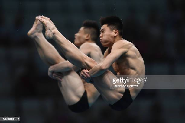 Myong Hyon II and Hyon Ju Ri of Democratic People's Republic of Korea compete during the Men's Diving 10M Synchro Platform preliminary round on day...