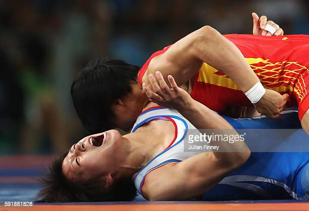 Myong Suk Jong of Republic of Korea competes against Xuechun Zhong of China during the Women's Freestyle 53 kg Repechage Round 2 match on Day 13 of...