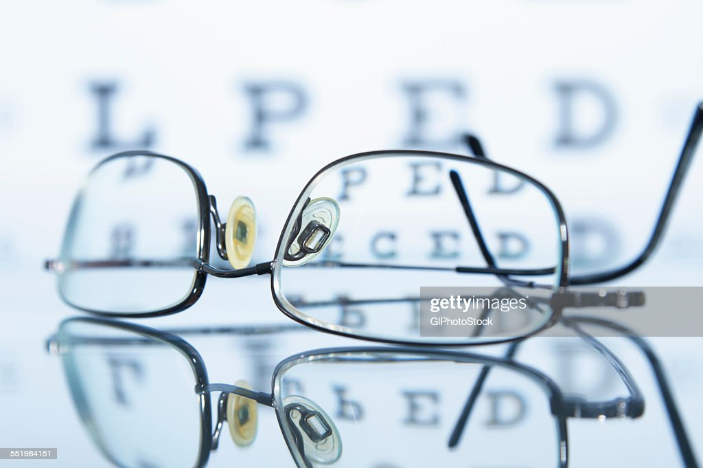 Myopic spectacles with a Snellen eye chart in the background : Stock Photo