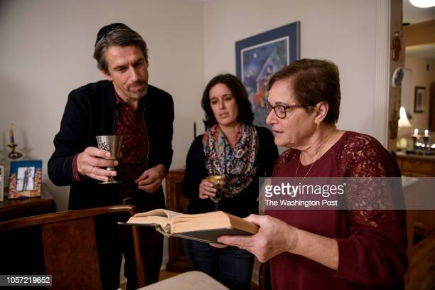 Myriam Gumerman right reads a prayer as she joins with her daughter Karen Kantz center and friend Machiel Keestra left as they celebrate the Shabbat...