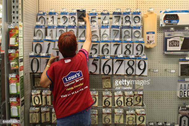 Myriam Torres restocks a display at a Lowe's store on the day the company reported a rise in earnings on March 1 2017 in Hialeah Florida Lowe's...