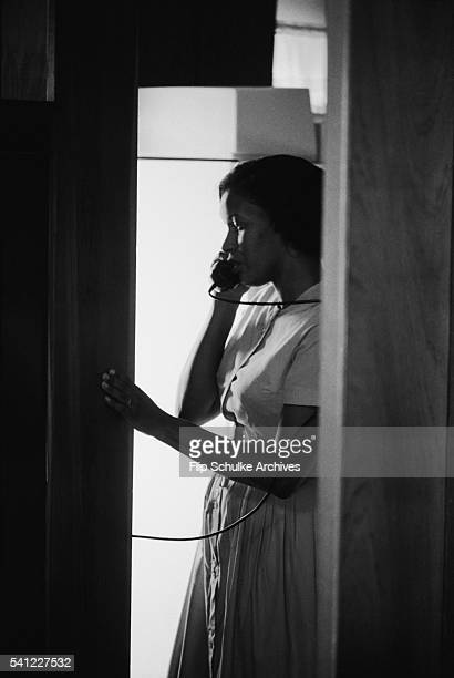 Myrlie Evers talks on a telephone in her house after the assassination of her husband Medgar Evers