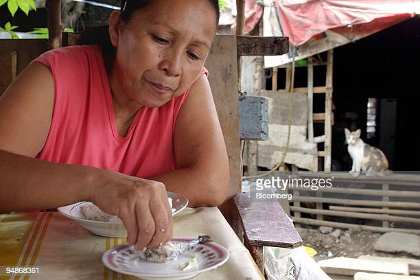 Myrna Lacdao eats a bowl of rice with a piece of dried fish in the urban poor community of San Roque in Quezon City the Philippines on Wednesday...