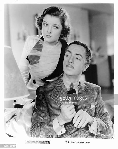 Myrna Loy leaning over William Powell as he holds the phone in publicity portrait for the film 'The Thin Man' 1934
