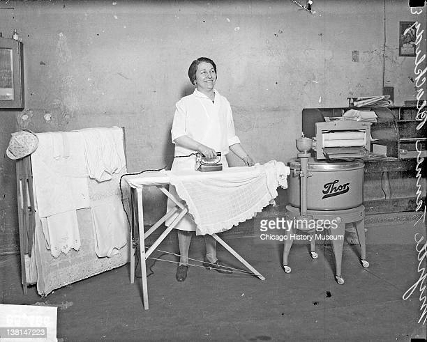 Myrtle T Blackridge ironing a shirt on an ironing board standing next to a washing machine Chicago Illinois 1928