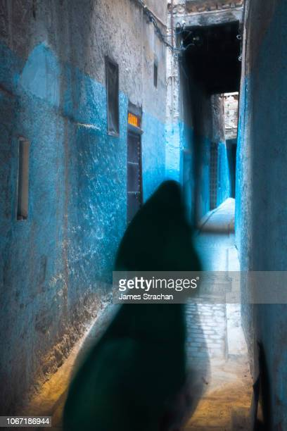 Mysterious blurred female figure, her traditional black dress flowing, disappears down an alleyway painted blue in the Old City (Medina) of Fez, UNESCO World Heritage Site, Morocco