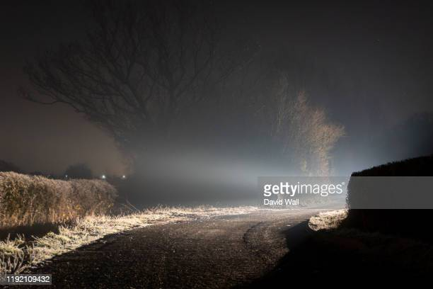 a mysterious bright light, glowing on a country lane, on a misty winters night - risk stock pictures, royalty-free photos & images
