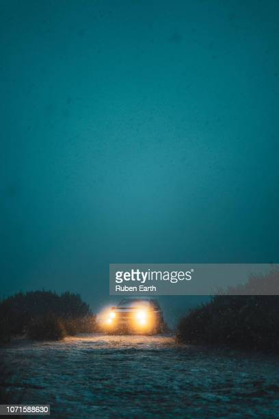 mysterious car in the fog and snow with the lights turned on - ティール色 ストックフォトと画像