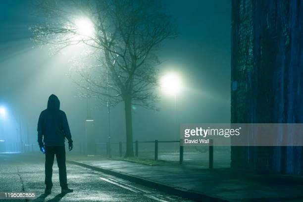 a mysterious figure standing by a city street light on a moody,  foggy atmospheric winters night - atmospheric mood stock pictures, royalty-free photos & images
