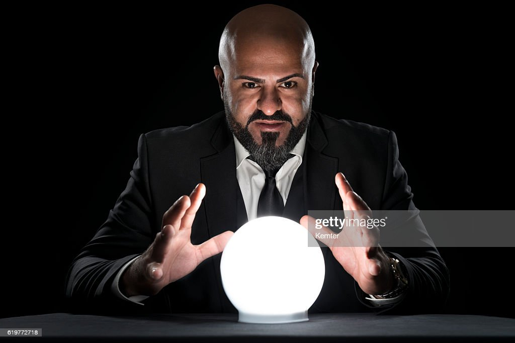 mysterious fortune teller gesturing at crystal ball : Stock Photo