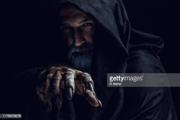 mysterious hooded man - grim reaper stock pictures, royalty-free photos & images