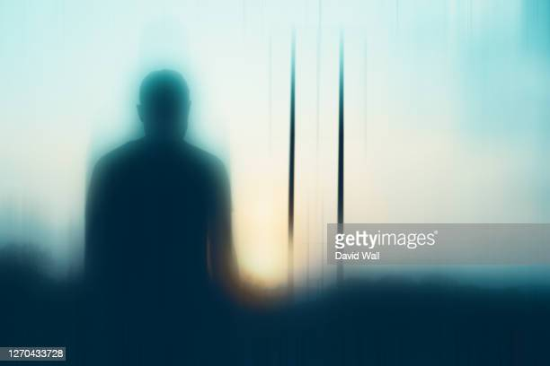 a mysterious male figure, silhouetted by the sun. with a blurred, out of focus edit. - defocussed stock pictures, royalty-free photos & images