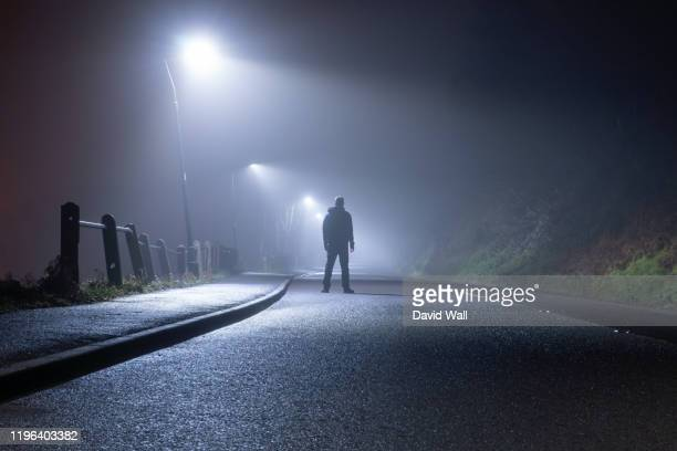 a mysterious man, alone, standing in the middle of a country road. under street lights. on a foggy, moody, spooky, winters night - in silhouette stock pictures, royalty-free photos & images