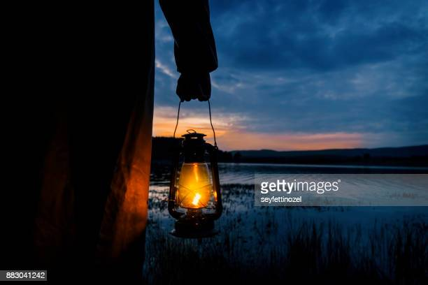 mysterious man in lake - oil lamp stock pictures, royalty-free photos & images