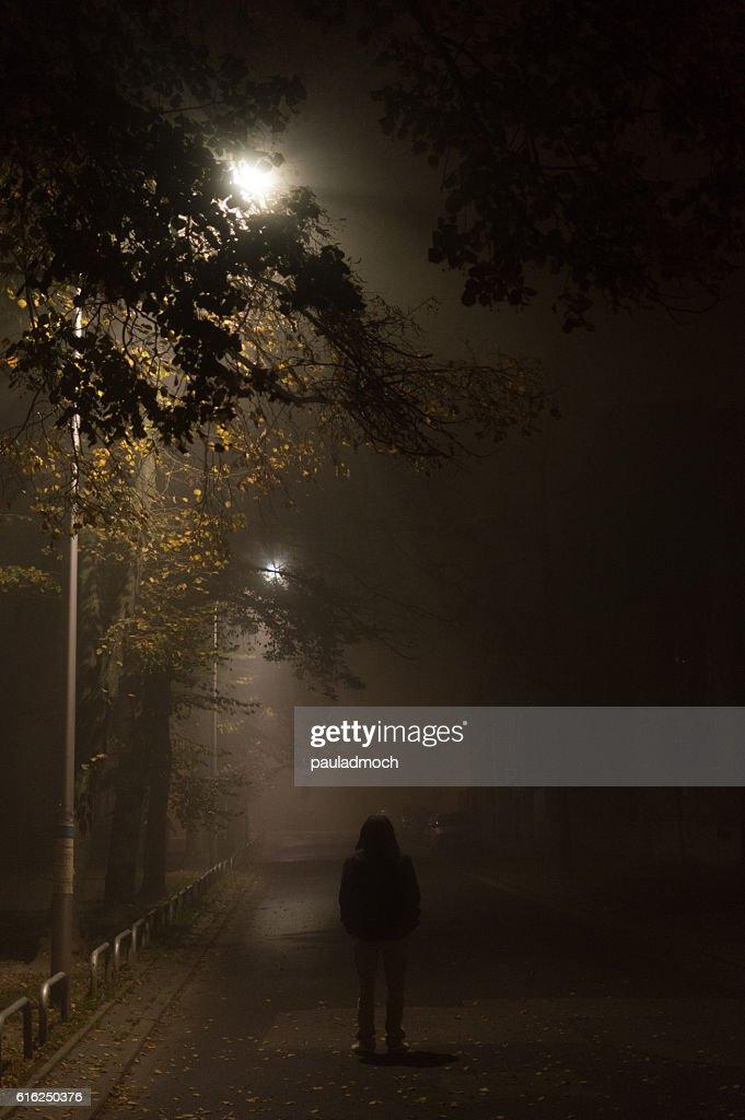 Mysterious man in the hood, alone on dark street : Foto de stock