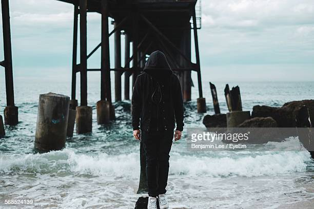 Mysterious Man Standing On Rock In Sea