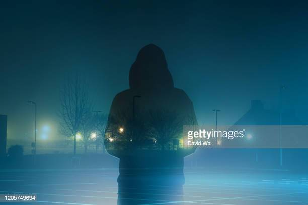 a mysterious moody hooded figure, silhouetted against back light with a double exposure of a urban scene on a foggy atmospheric winters night. - parking stock pictures, royalty-free photos & images