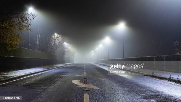 a mysterious moody straight road at night on a foggy winters evening. with street lights glowing in the dark. - fog stock pictures, royalty-free photos & images