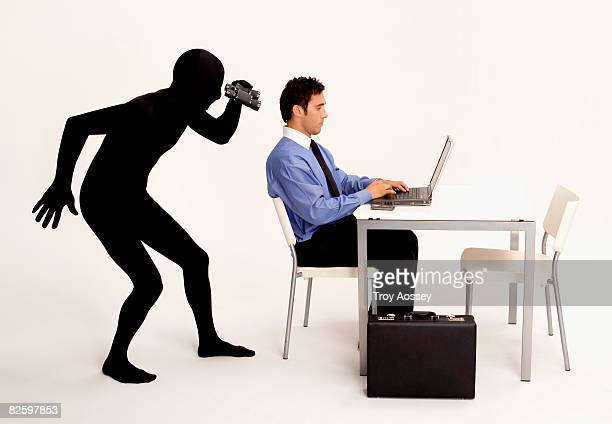 Mysterious person looking at  mans computer