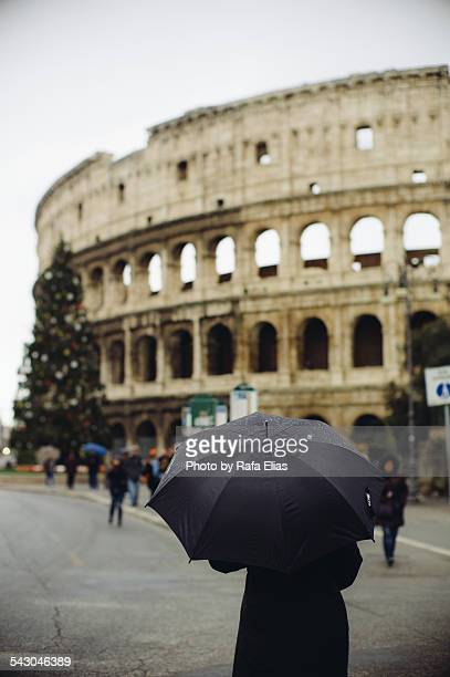 Mysterious person with umbrella by Colosseum