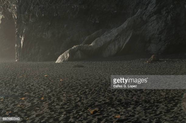 mysterious rock formation on black sand beach - basalt stock pictures, royalty-free photos & images