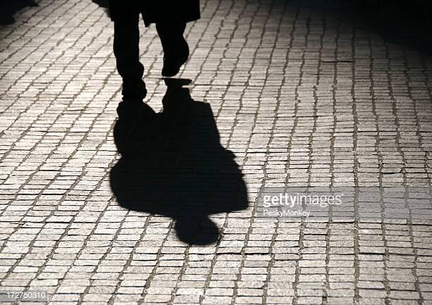 Mysterious Shadow Figure of Businessman Walking on Cobblestones