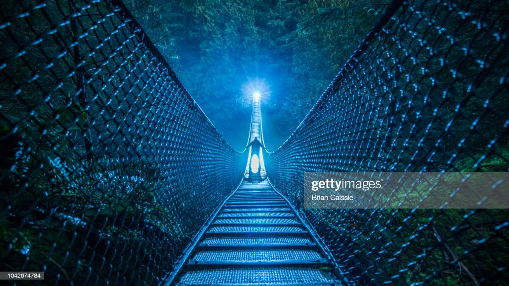 Mysterious silhouetted person on suspension bridge in woods at night : Stock Photo