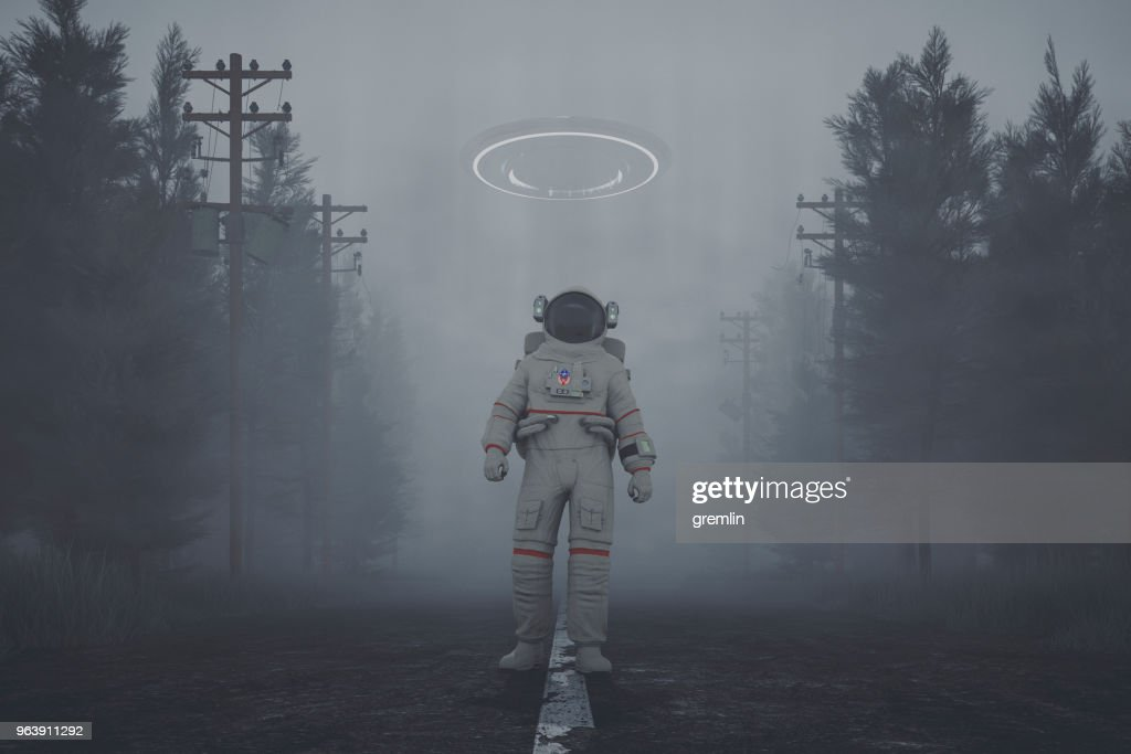 Mysterious UFO and walking astronaut on the forest road at night : Stock Photo