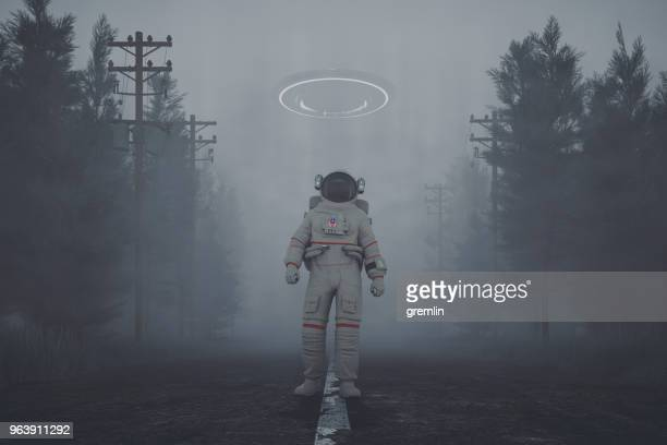 mysterious ufo and walking astronaut on the forest road at night - conspiracy stock pictures, royalty-free photos & images
