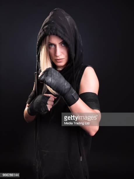 Femme mystérieuse, un combattant en hoodie posant en position de combat
