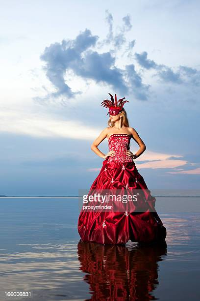 Mysterious woman in red dress with carnival mask
