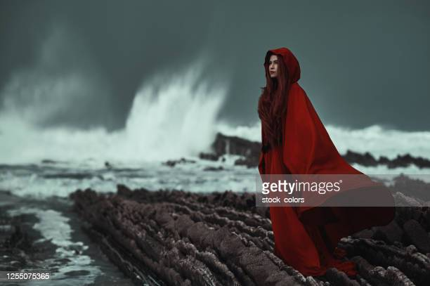 mysterious woman wearing red on the coastline - cape stock pictures, royalty-free photos & images