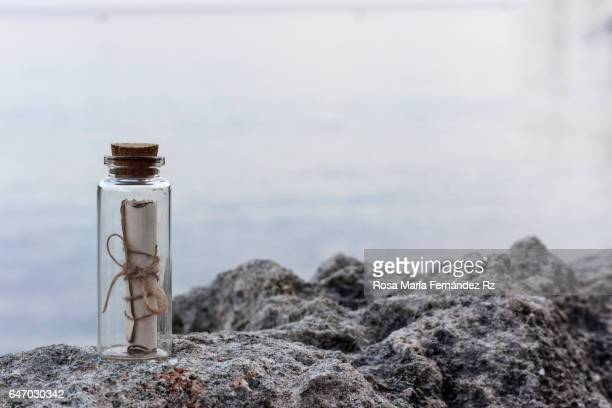 mysterius message in a bottle on a stone in a beach on natural background. - storytelling stock pictures, royalty-free photos & images