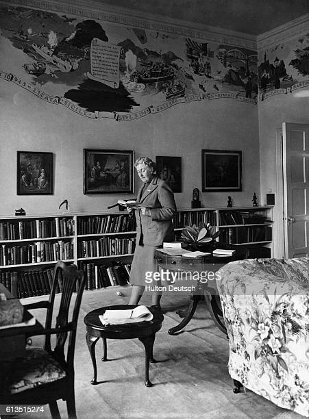 Mystery writer Agatha Christie reads in her library at Greenway House