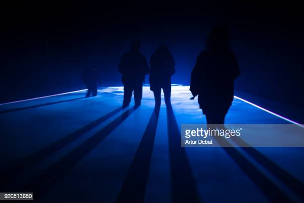 Mystic picture of silhouette of people walking at night with blue light.