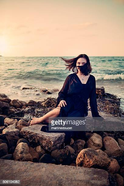 Mystical young woman at the beach, sunset, connecting with nature.