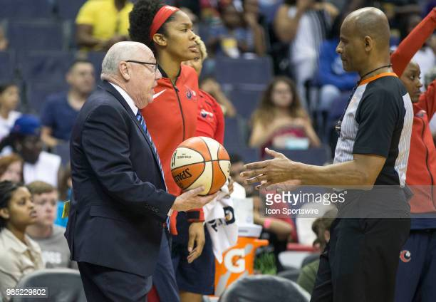 Mystics coach Mike Thibault hand the ball to an official during a WNBA game between the Washington Mystics and the Connecticut Sun on June 26 at...