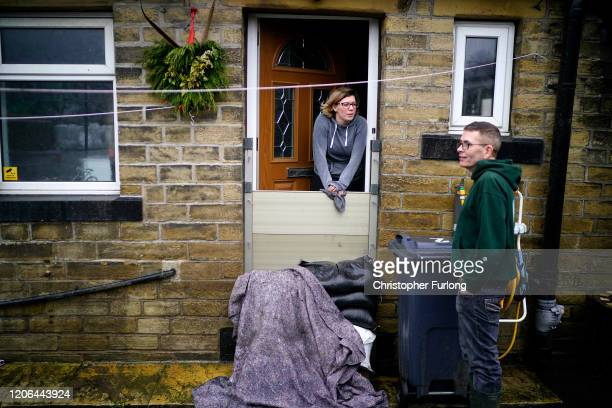 Mytholmroyd residents look out over the flood defences as soldiers arrive to help shore up flood barriers and Storm Dennis begins to make landfall in...