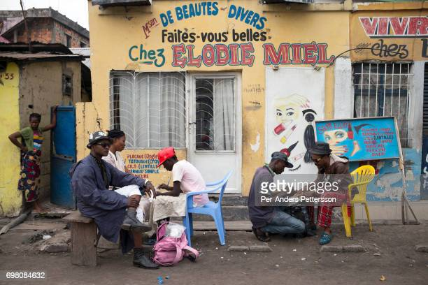 Mzee Kindingu the leader of the Sapeurs group The Leopards get a manicure with a fellow Sapeur o on February 3 2015 in the streets of Kinshasa DRC...