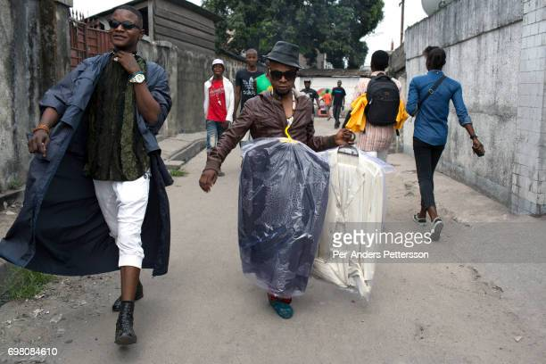 Mzee Kindingu the leader of the Sapeurs group The Leopards picks up some clothes from a drycleaner on February 3 2015 in Kinshasa DRC The word Sapeur...
