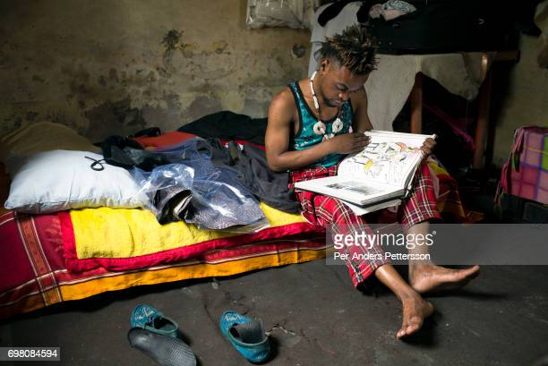 Mzee Kindingu the leader of the Sapeurs group The Leopards reads in a fashion book in his bedroom on February 3 2015 in Kinshasa DRC The word Sapeur...