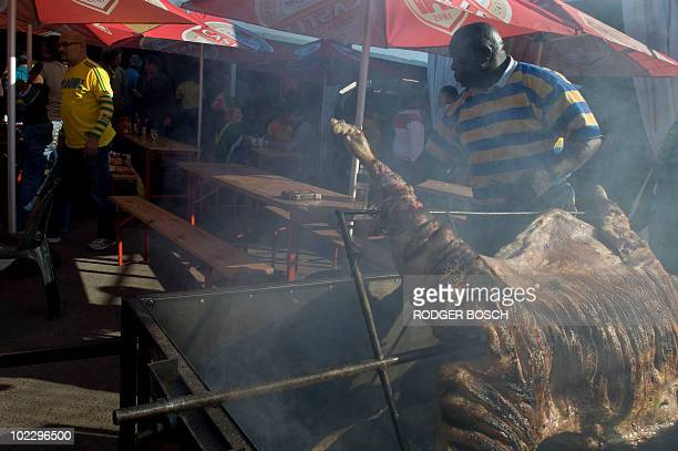 Mzwai Ncedani cooks a sheep for football fans at Mzoli's Tavern and Butcher in Gugulethu township 20kms from Cape Town on June 22 2010 South Africa's...
