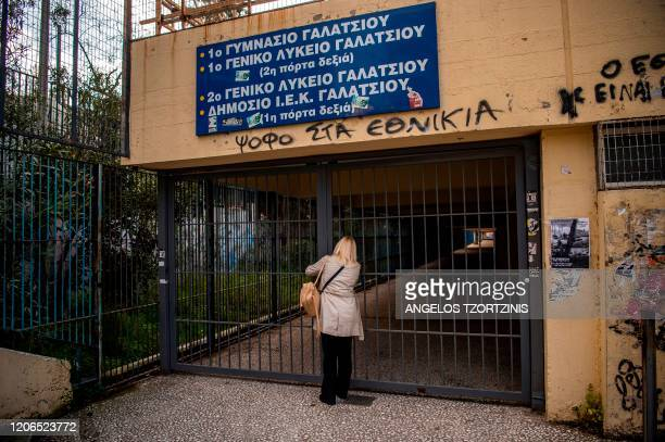 n employee locks the entrance of a school in the centre of Athens on March 11 2020 Greece on March 10 2020 announced a twoweek shutdown of schools...