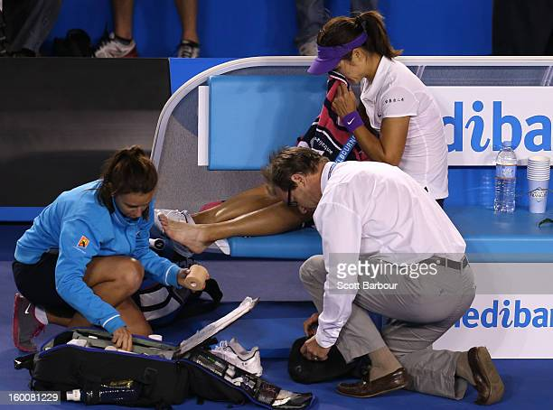 Na Li of China has her ankle strapped by medical staff in her women's final match against Victoria Azarenka of Belarus during day thirteen of the...