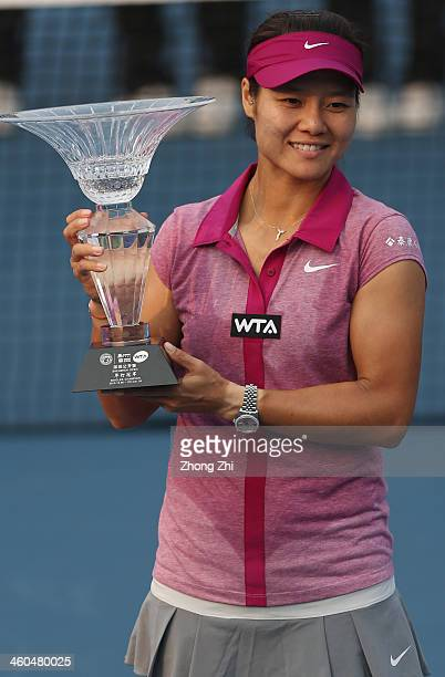 Na Li of China holds the champion trophy after winning her match against Shuai Peng of China on day eight of the WTA Shenzhen Open at Shenzhen...